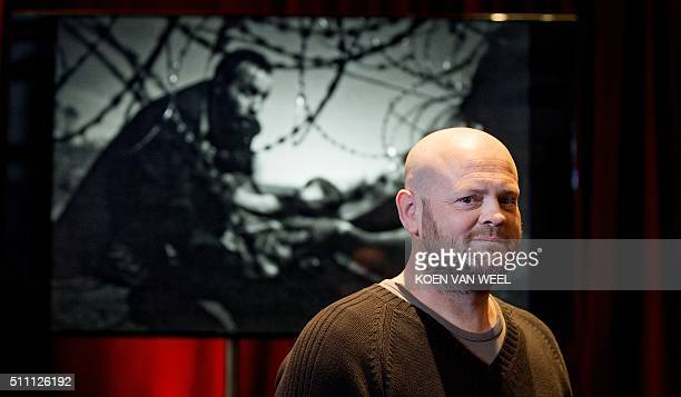 Australian Budapestbased freelance photographer Warren Richardson poses in front of his picture 'Hope for a New Life' on February 18 2016 in...