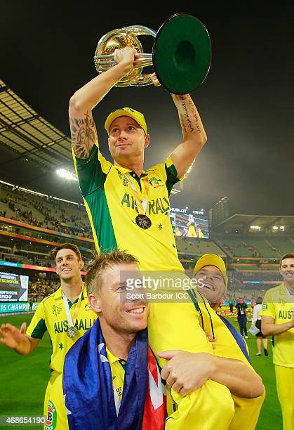 Australian captain Michael Clarke is lifted up by teamates David Warner and Aaron Finch as he holds the World Cup trophy aloft as they celebrate...