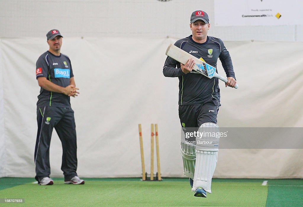 Australian captain Michael Clarke runs as Australian Cricket Team Physiotherapist Alex Kountouris (L) looks on during an Australian nets session at Melbourne Cricket Ground on December 25, 2012 in Melbourne, Australia.
