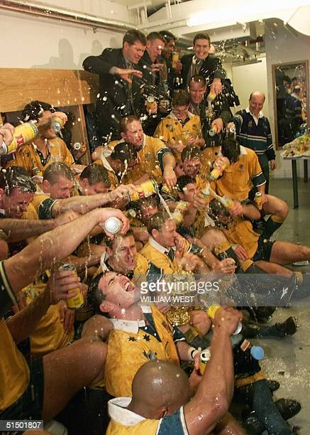 Australian center Daniel Herbert celebrates as his teammates pour beer all over him in the locker room after the Rugby World Cup 1999 final game...
