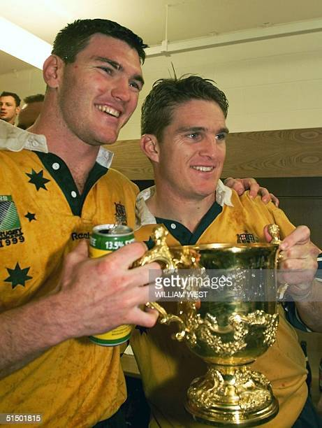 Australian centers Daniel Herbert and Tim Horan pose with the cup inside the locker room after the Rugby World Cup 1999 final game between France and...