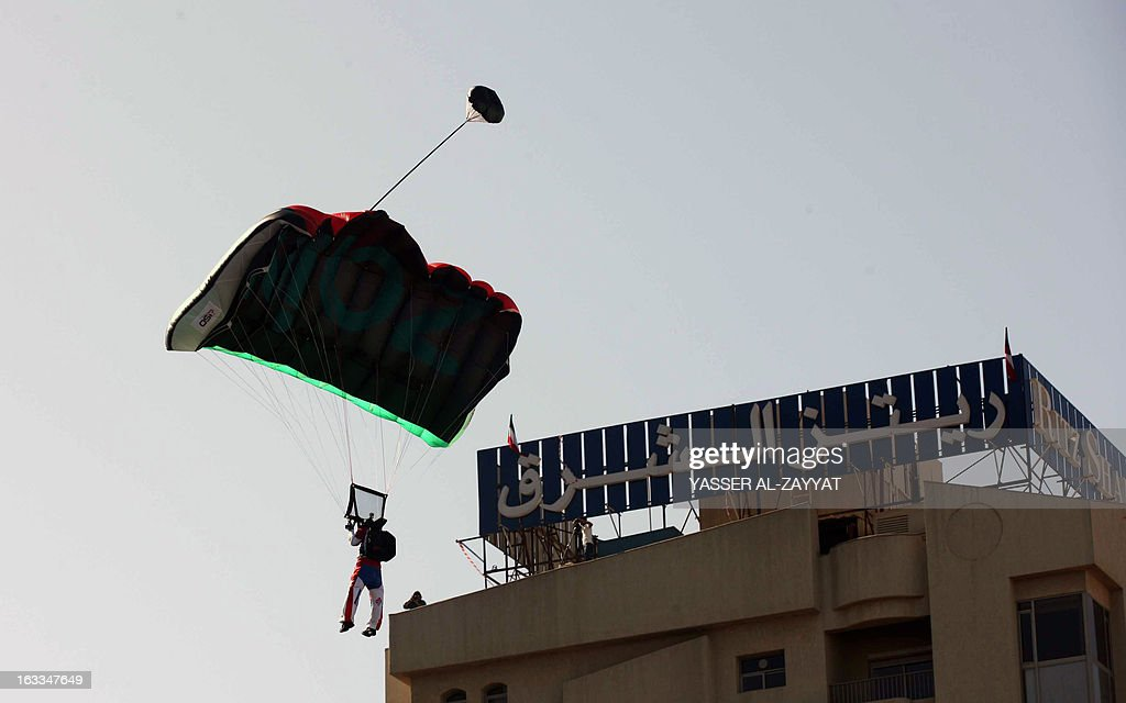 Australian Chris McDougall has his parachute deployed after jumping from Al-Hamra Tower, the tallest building in Kuwait, on March 8, 2013, in Kuwait city. Al-Hamra Tower is 414 meters high above sea-level and Kuwait's tallest tower, which has become a landmark. McDougall holds the record for trouble-free jumps, with 2,600 base jumps and 10,000 sky jumps. AFP PHOTO YASSER AL-ZAYYAT