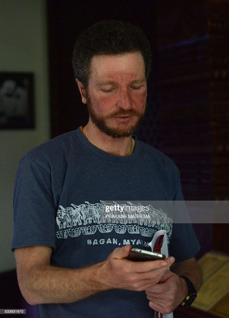 Australian climber Robert Gropel uses a cellular telephone as he stands in a hotel lobby in Kathmandu on May 24, 2016, after being rescued from Mount Everest. Gropel's wife Maria Strydom died on May 21, while descending from the summit of Mount Everest from high-altitude sickness. The Australian climber was on her way down from Camp 4 to Camp 3 when she fell ill and died on, Pasang Phurba Sherpa, a board director at Seven Summit Treks, told AFP. / AFP / PRAKASH