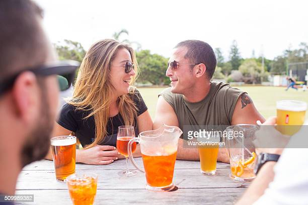 Australian couple drinking with friends in beer garden bowling club