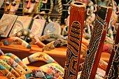 Didgeridoos on background of blurred aboriginal souvenirs, including boomerangs.