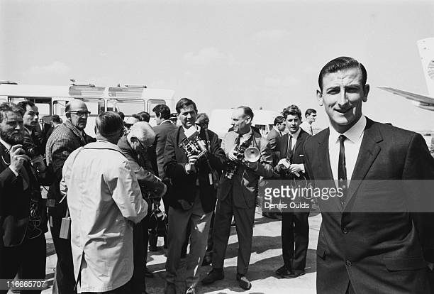 Australian cricket captain Bill Lawry surrounded by photographers as he arrives with the rest of the Australian touring team at Heathrow Airport...