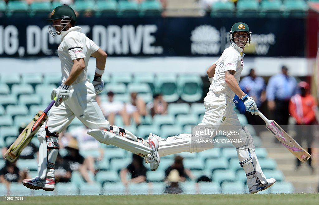 Australian cricket captain Michael Clarke (R) and teammate Ed Cowan run between the wickets on the fourth day of the third cricket Test match between Australia and Sri Lanka at the Sydney Cricket Ground on January 6, 2013.