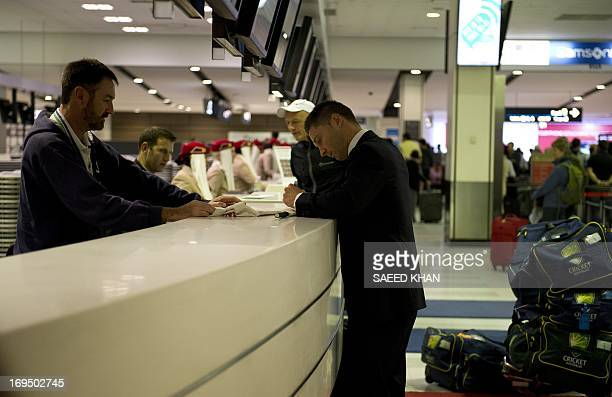Australian cricket captain Michael Clarke gives an autograph to a cricket fan at the checkin counter of Sydney International Airport on May 26 2013...