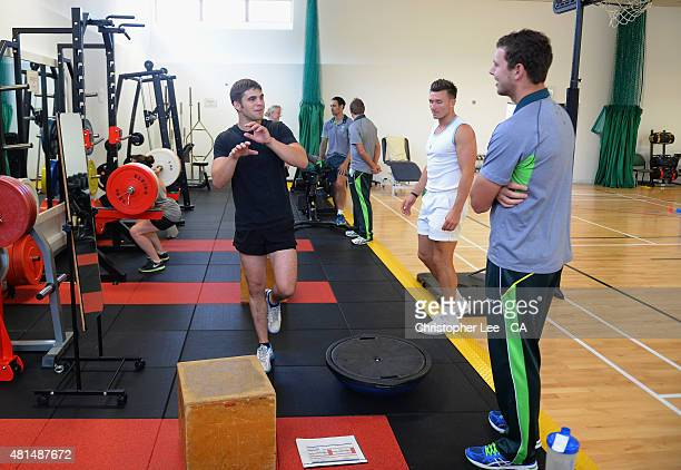 Australian cricket player Josh Hazelwood talks to a patient in the gym with Mitchel Johnson and Ryan Harris as they visit Headley Court Military...