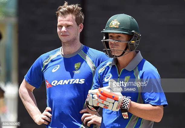 Australian cricket team captain Steven Smith and his teammate David Warner watch others during a practice session at the Warner Park stadium in...
