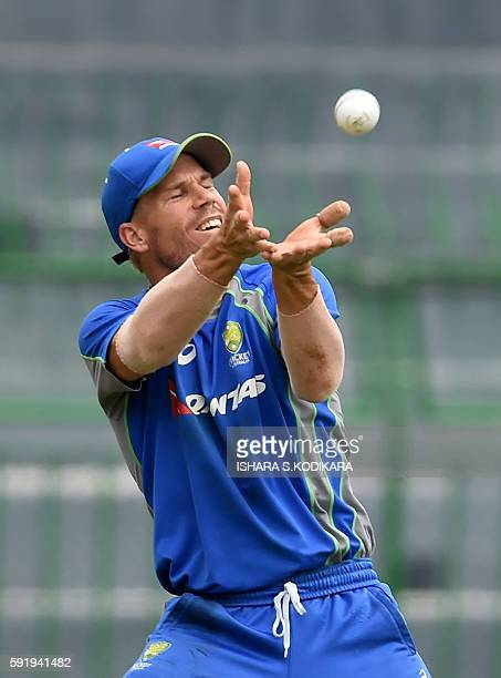 Australian cricketer David Warner catches a ball during a practice session at the R Premadasa Cricket Stadium in Colombo on August 19 2016 Australia...