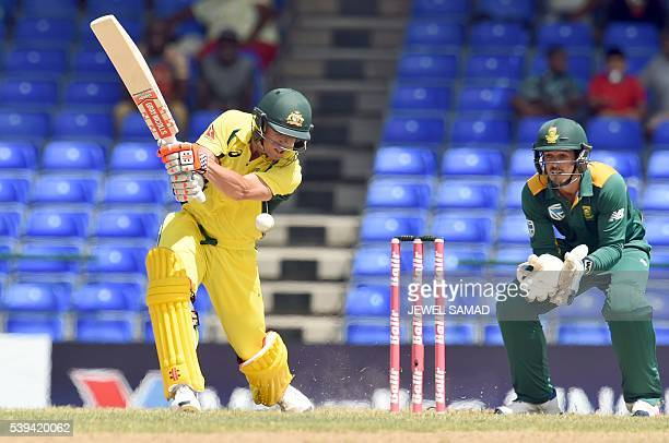 Australian cricketer David Warner plays a shot as South African wicketkeeper Quinton de Kock looks on during their Trination series One Day...
