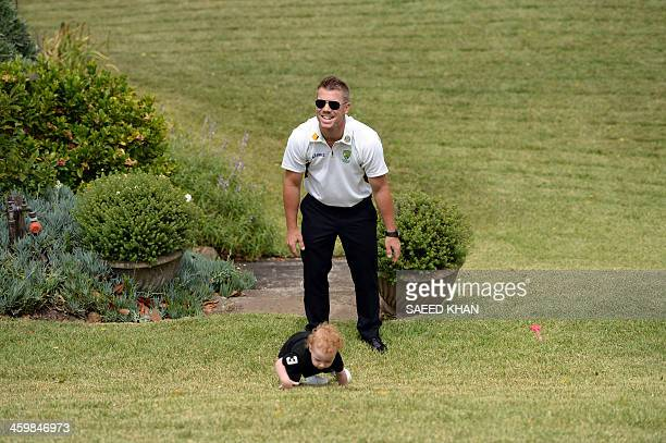 Australian cricketer David Warner plays with a child during a New Year's Day reception hosted by the Australian Prime Minister Tony Abbott for...