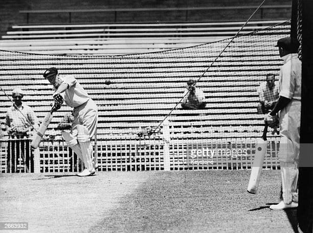 Australian cricketer Don Bradman gives a batting lesson to Bill Brown before the fifth Test against India