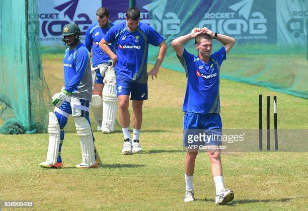 Australian cricketer Jackson Bird walks over the field with his teammates during a training session at the ShereBangla National Cricket Stadium in...