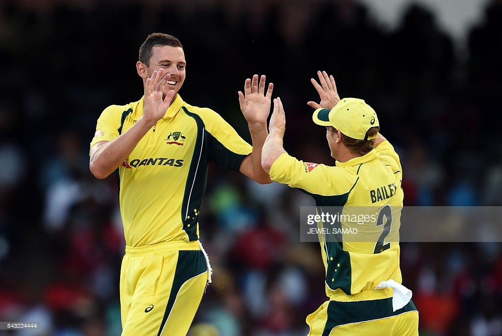 Australian cricketer Josh Hazlewood (L) celebrates with teammate George Bailey after dismissing West Indies batsman Andre Fletcher during the final match of the Tri-nation Series between Australia and West Indies in Bridgetown on June 26, 2016. / AFP / Jewel SAMAD