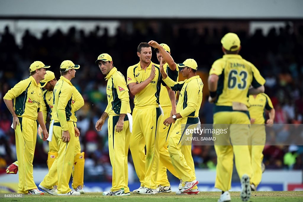 Australian cricketer Josh Hazlewood (C) celebrates with teammates after dismissing West Indies batsman Andre Fletcher during the final match of the Tri-nation Series between Australia and West Indies in Bridgetown on June 26, 2016. / AFP / Jewel SAMAD