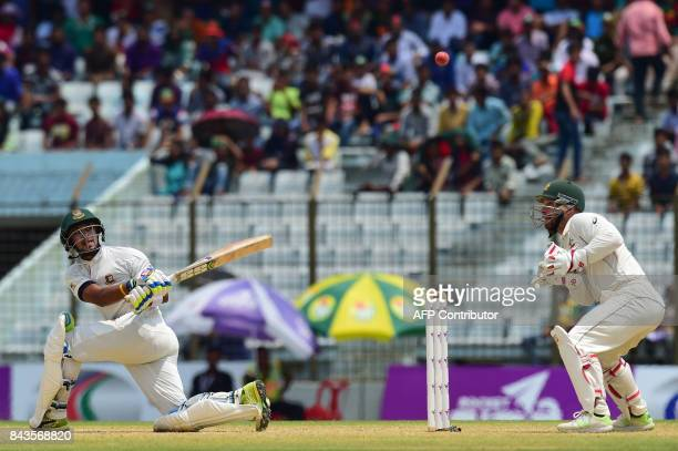 Australian cricketer Matthew Wade looks on as Bangladeshi cricketer Sabbir Rahman plays a shot during the fourth day of the second cricket Test...