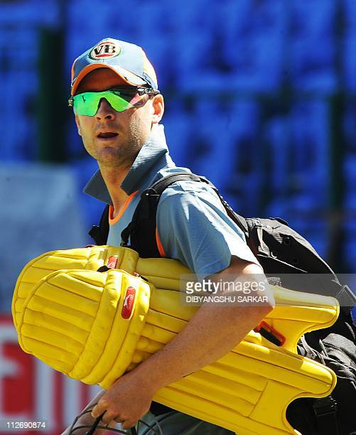 Australian cricketer Michael Clarke carries his batting gear to a training session at the National Cricket Academy in Bangalore on February 14 ahead...