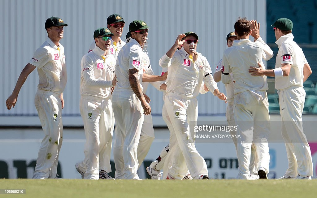 Australian cricketer Michael Hussey (C) celebrates with teammates after taking a catch to dismiss unseen Sri Lankan batsman Thilan Samaraweera on day three of the third cricket Test match between Australia and Sri Lanka at the Sydney Cricket Ground on January 5, 2013. AFP PHOTO/ MANAN VATSYAYANA USE