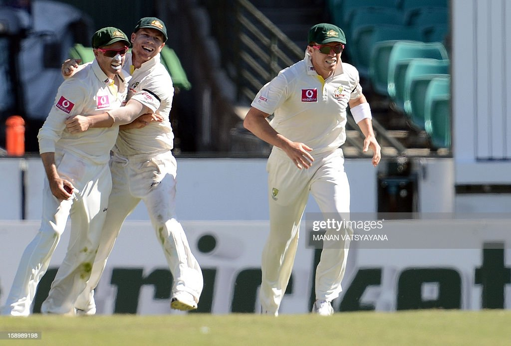Australian cricketer Michael Hussey (L) celebrates with teammates David Warner (C) and Peter Siddle (R) after taking a catch to dismiss unseen Sri Lankan batsman Thilan Samaraweera on day three of the third cricket Test match between Australia and Sri Lanka at the Sydney Cricket Ground on January 5, 2013.