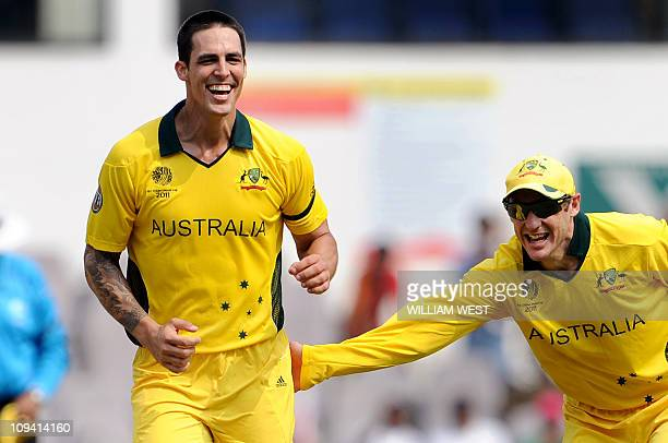 Australian cricketer Mitchell Johnson is congratulated by teammate David Hussey after dismissing unseen New Zealand batsman James Franklin during the...