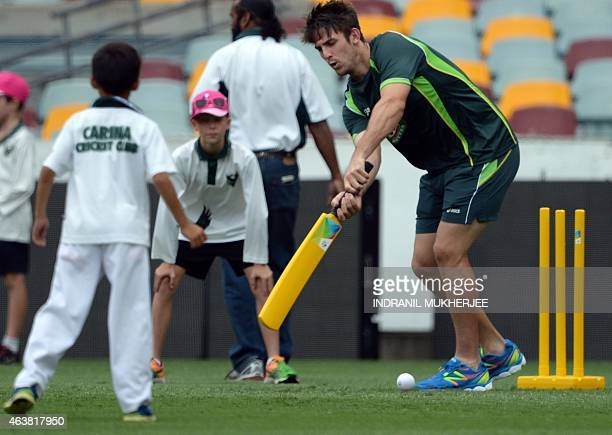 Australian cricketer mitchell Marsh plays a game of tennis ball cricket with kids after a training session of the 2015 Cricket World Cup at The Gabba...