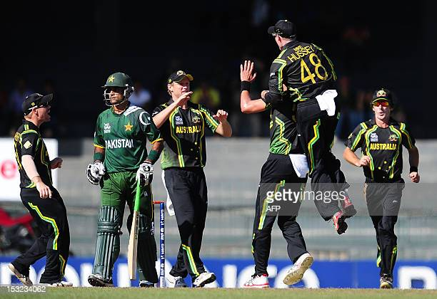 Australian cricketer Mitchell Starc celebrates with teammates his dismissal of Pakistan cricket captain Mohammad Hafeez during the ICC Twenty20...