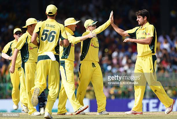 Australian cricketer Moises Henriques celebrates with teammates after he dismissed Sri Lanka cricketer Tillakaratne Dilshan during the first One Day...