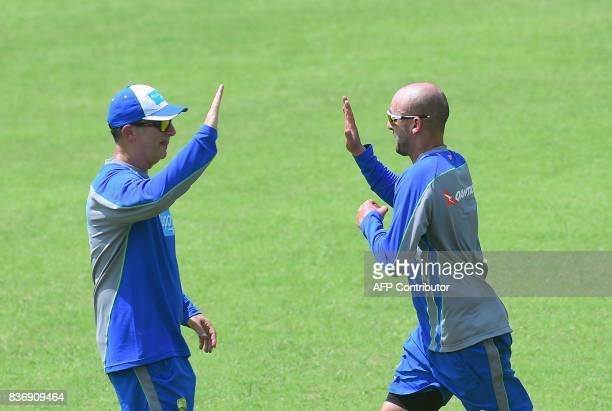 Australian cricketer Nathan Lyo takes a high five with support staff during a training session at the ShereBangla National Cricket Stadium in Dhaka...