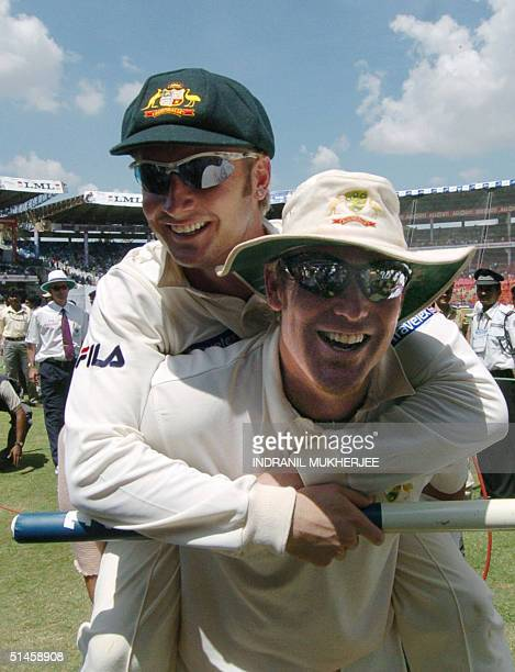 Australian cricketer Shane Warne carries teammate Michael Clarke piggy back as he walks back to the pavillion after triumphing over India on the...