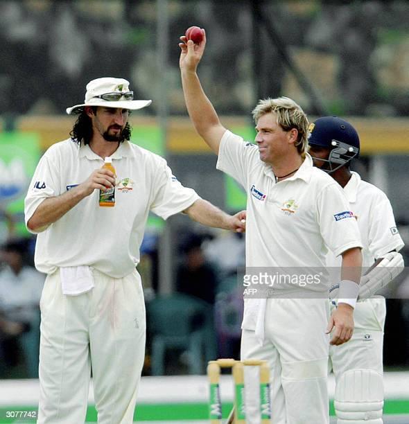 Australian cricketer Shane Warne raises the ball as he celebrates after dimissing Sri Lankan captain Hashan Tillakaratne bringing him to a total of...