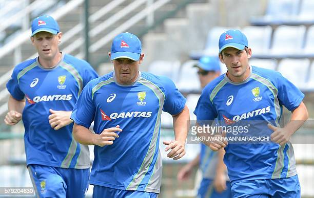 Australian cricketer Stephen O'Keefe and teammates warm up during a practice session at the Pallekele International Cricket Stadium in Pallekele on...