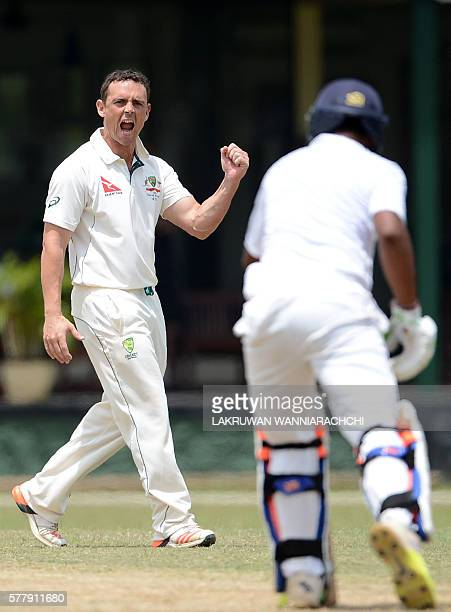 Australian cricketer Stephen O'Keefe celebrates after he dismissed Sri Lankan XI cricketr Asela Gunaratne during the third day of a three day...