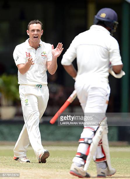 Australian cricketer Stephen O'Keefe celebrates after he dismissed Sri Lankan XI cricketr Shehan Jayasuriya during the third day of a three day...