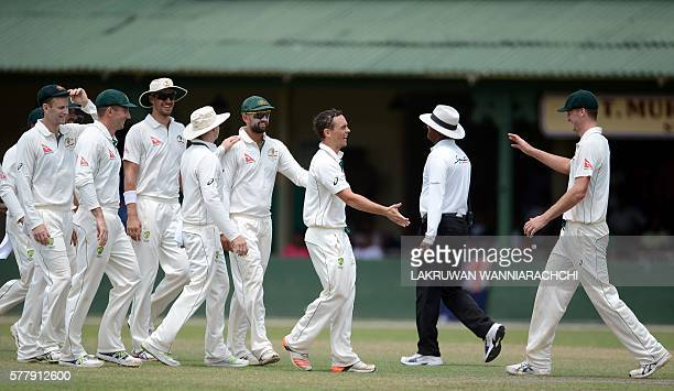 Australian cricketer Stephen O'Keefe celebrates with teammates after he dismissed Sri Lankan XI batsman Dasun Shanaka during the third day of a three...