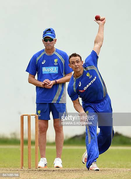 Australian cricketer Stephen O'Keefe delivers a ball as bowling coach Allan Donald looks on during a practice session at the R Premadasa Cricket...