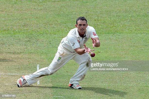 Australian cricketer Stephen O'Keefe takes a catch to dismiss Sri Lankan XI cricketer Chaturanga de Silva during the first day of a three day...