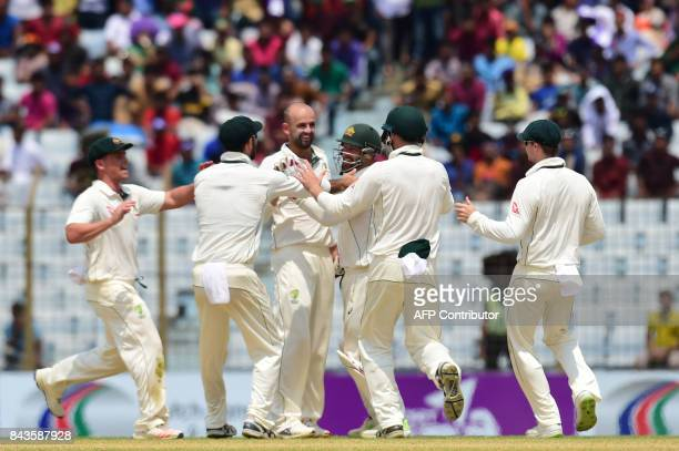 Australian cricketers congratulate teamamte Nathan Lyon after the dismissal of Bangladeshi cricketer Sabbir Rahman tries to makes his ground during...