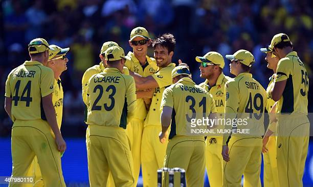 Australian cricketers congratulate teammate Mitchell Johnson after taking a catch off his own bowling to dismiss New Zealand batsman Kane Williamson...