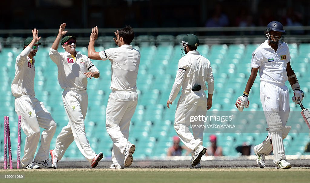 Australian cricketers congratulate teammate Mitchell Johnson (C) after taking the wicket of Sri Lankan batsman Suranga Lakmal on the fourth day of the third cricket Test match between Australia and Sri Lanka at the Sydney Cricket Ground on January 6, 2013.