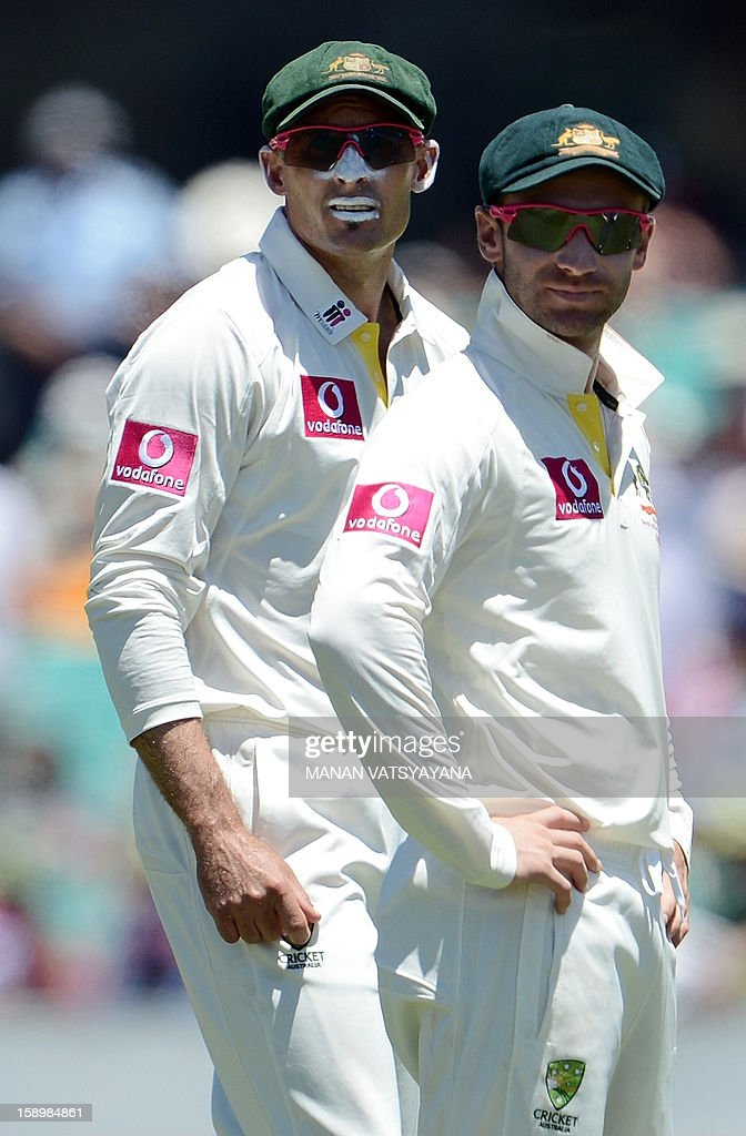 Australian cricketers Mike Hussey (L) and Philip Hughes (R) look at the giant screen to watch the dismissal of unseen Sri Lankan batsman Tilakaratne Dilshan on day three of the third cricket Test between Australia and Sri Lanka at the Sydney Cricket Ground on January 5, 2013.