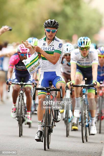 Australian cyclist Patrick Lane of team UniSaAustralia pics up supplies at the front of the peloton as he goes through the hydration station competes...
