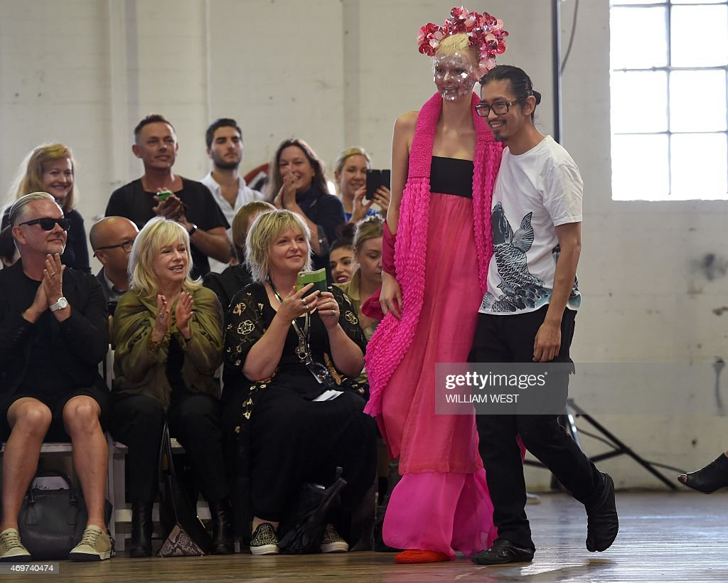 Australian designer Akira Isogawa walks with a model as he acknowledges the applause after a parade of his label Akira at Fashion Week Australia in...