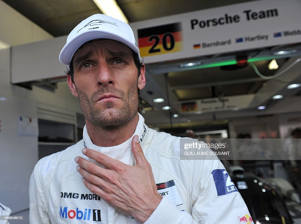 Australian driver Mark Webber (Porsche 919 Hybrid N° 20) speaks with journalists in a pit during the 82nd edition of the Le Mans 24-hours (24 Heures du Mans) endurance race, on June 15, 2014 in Le Mans, western France. Austrialian former Formula One ace Mark Webber was leading the Le Mans 24 Hours endurance race with just three hours to go today after cashing in on the Audi team's misfortunes. AFP PHOTO / GUILLAUME SOUVANT