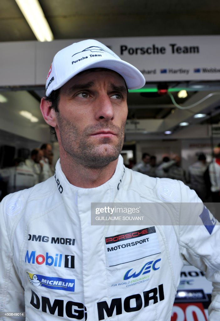 Australian driver Mark Webber (Porsche 919 Hybrid N° 20) speaks with journalists in a pit during the 82nd edition of the Le Mans 24-hours (24 Heures du Mans) endurance race, on June 15, 2014 in Le Mans, western France. Austrialian former Formula One ace Mark Webber was leading the Le Mans 24 Hours endurance race with just three hours to go today after cashing in on the Audi team's misfortunes.