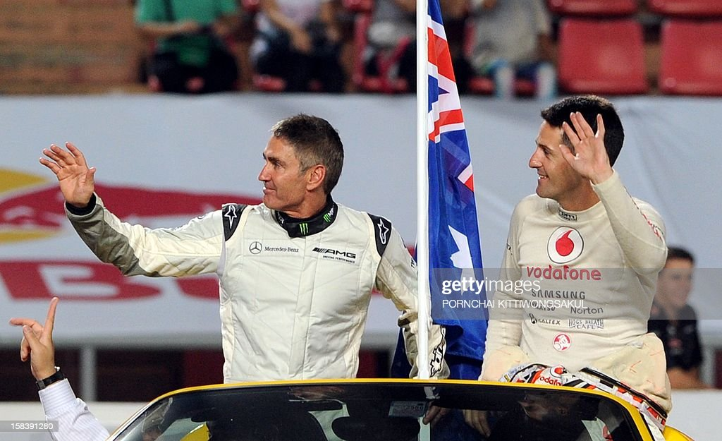 Australian drivers Michael Doohan (L) and Jamie Whincup (R) waves to fans during the Race of Champions (ROC) Nations Cup Drivers 's Presentation at Rajamangala Stadium in Bangkok on December 15, 2012. The Race of Champions (ROC) will take place in Thailand between December 14 and 16 and brings together heavyweights from all motor racing disciplines in the same type of car.