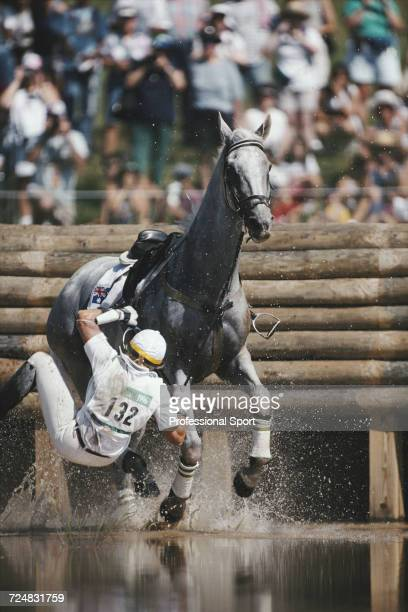 Australian equestrian Gillian Rolton falls from her horse Peppermint Grove at the water hazard in the Cross Country discipline during competition for...