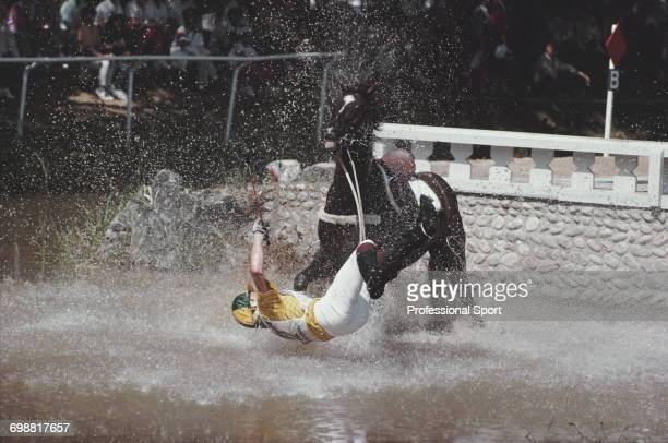 Australian equestrian Scott Keach pictured in action for Australia falling from his horse 'Trade Commissioner' at the water jump during competition...