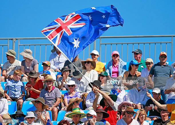 Australian fans in the crowd wave a large Australian flag as they watch the reverse singles match between Sam Groth of Australia and Mikhail...